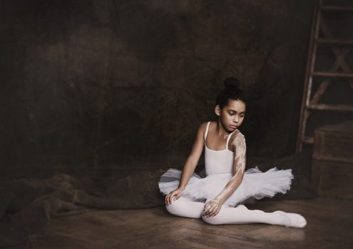 Little adagio ballet dancer sitting on the floor