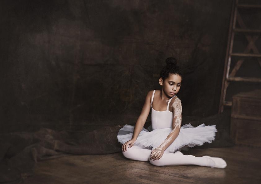 Little adagio ballet dancer sitting on the floor
